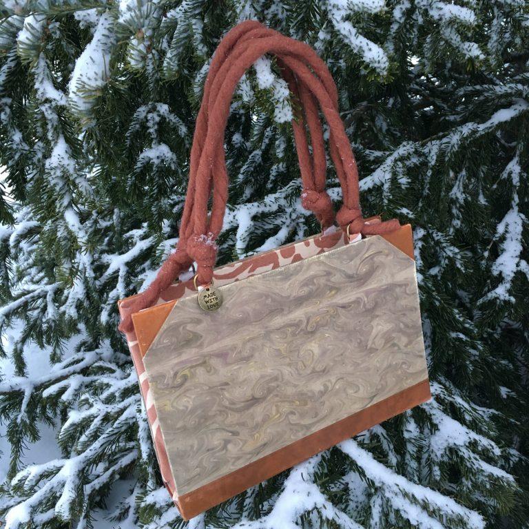 Kirjalaukku roikkuu lumisen kuusen oksalla.