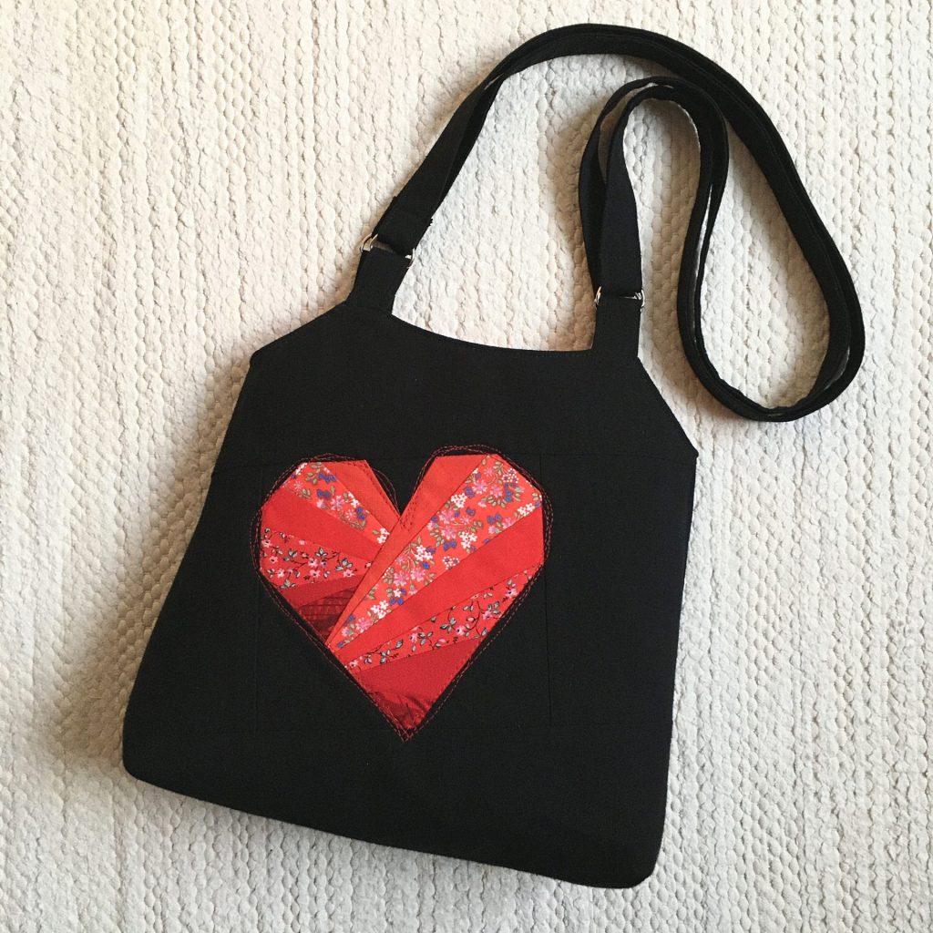 Musta laukku jossa punainen sydän keskellä.