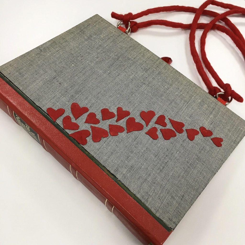 """Harmaa kirjalaukku, jonka kyljessä pieniä punaisia sydämiä. Tehty kirjasta """"Sydämellinen lääkäri""""."""