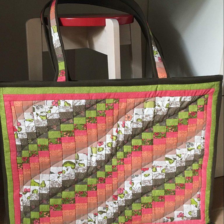 Iso tilkkulaukku, jossa oransseja vinoja raitoja, hieman vihreää ja mustavalkoinen tausta.