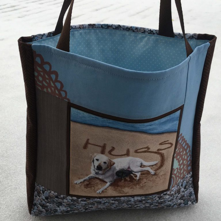 """Sini-ruskea laukku jossa keskellä kuva koirasta ja teksti """"Hugs""""."""